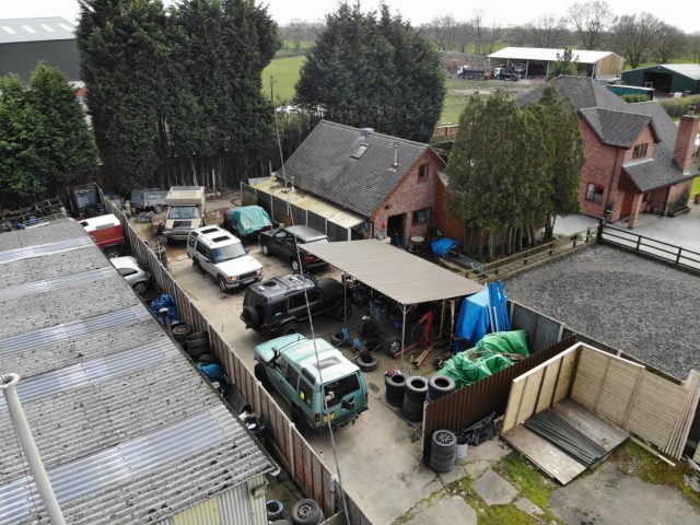 A gaggle of Land Rovers in a yard